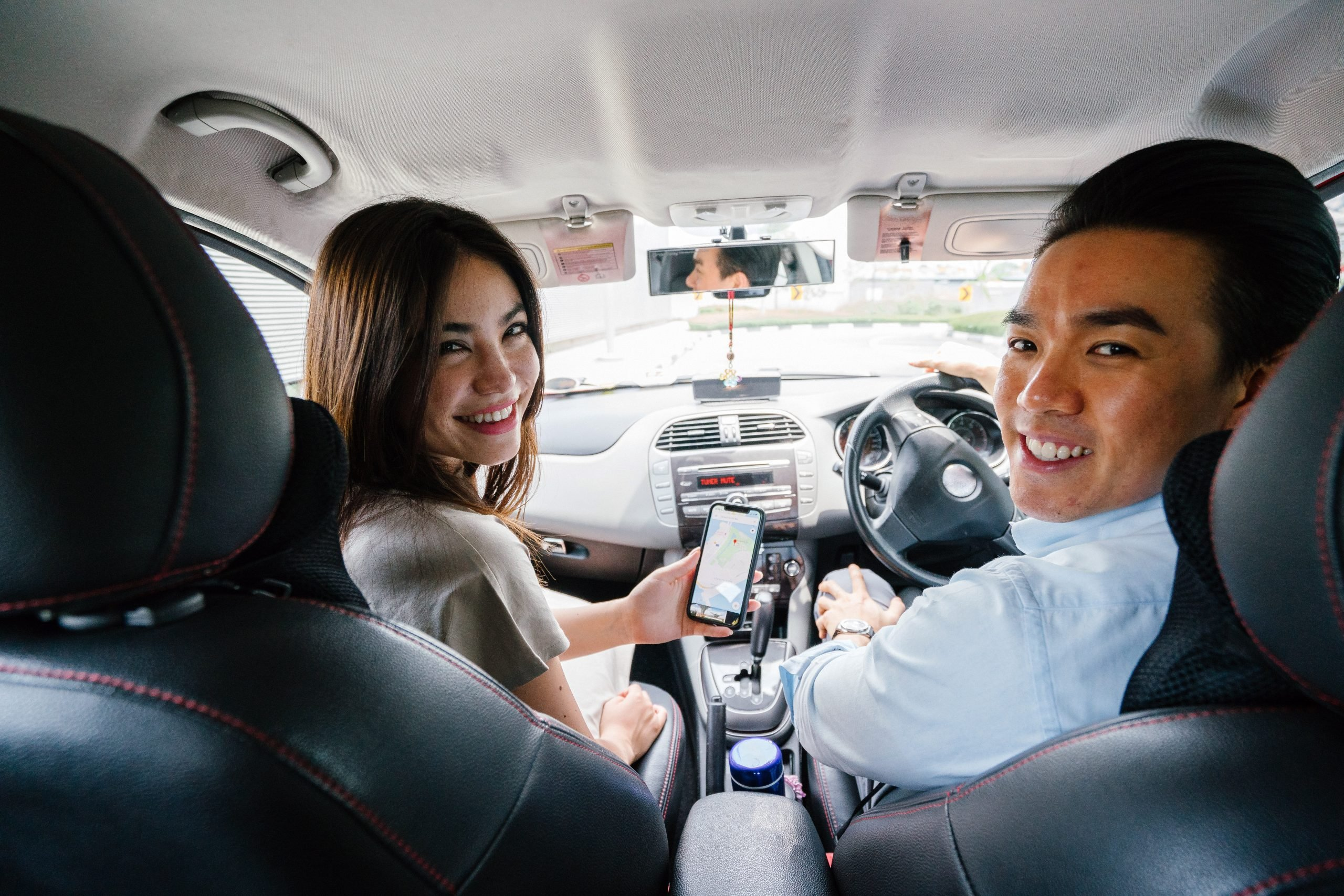 smiling-man-and-woman-sitting-inside-vehicle-1399287