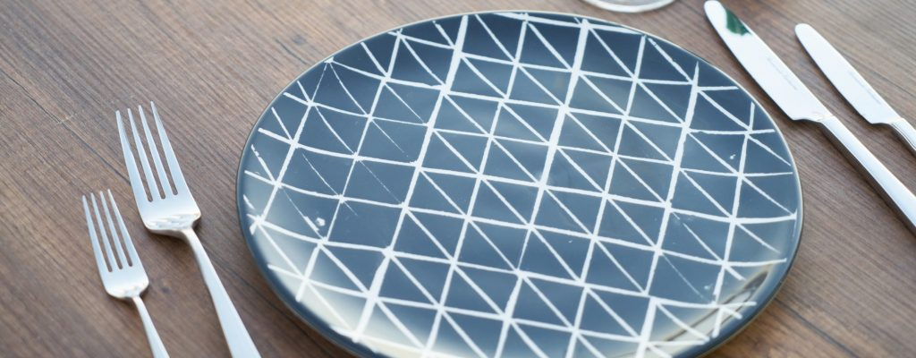 round-blue-and-white-ceramic-plate-two-forks-two-knives-and-1907642